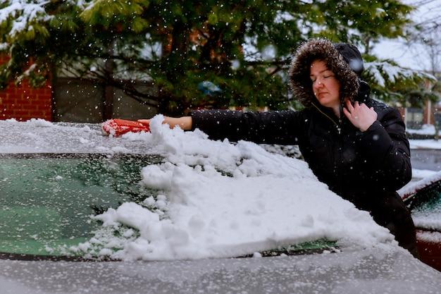 Jovem mulher está varrendo a neve de seu carro Foto Premium