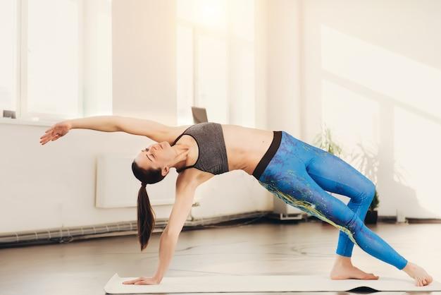 Jovem mulher esticando e fazendo exercícios de ioga no estúdio Foto Premium