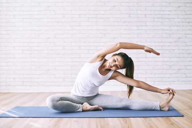 Jovem mulher esticando no chão como broca de manhã para desenvolver flexibilidade Foto gratuita