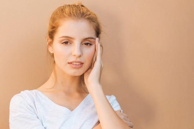 Jovem mulher estressante com a mão no rosto contra fundo bege Foto gratuita
