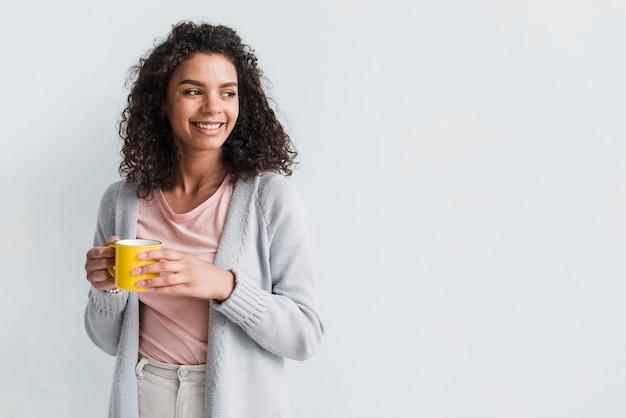 Jovem mulher étnica que guarda o copo no fundo branco Foto gratuita