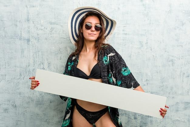 Jovem mulher europeia usando biquíni e segurando um cartaz Foto Premium