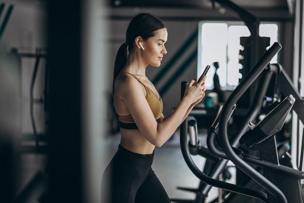 Jovem mulher exercitando na academia elíptica Foto gratuita