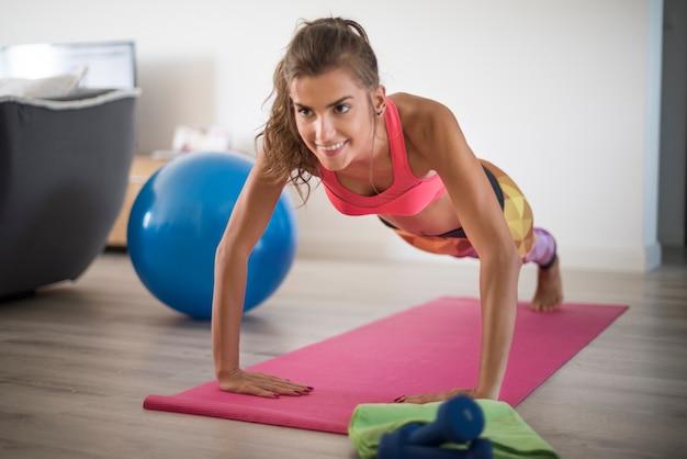 Jovem mulher exercitando-se em casa. esta mulher tem uma resistência tão grande Foto gratuita