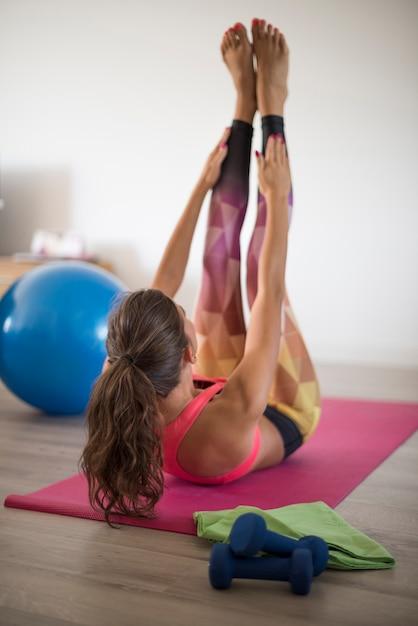 Jovem mulher exercitando-se em casa. este é um dos exercícios mais difíceis Foto gratuita
