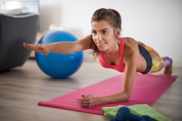 Jovem mulher exercitando-se em casa. satisfação tirada do exercício em casa Foto gratuita