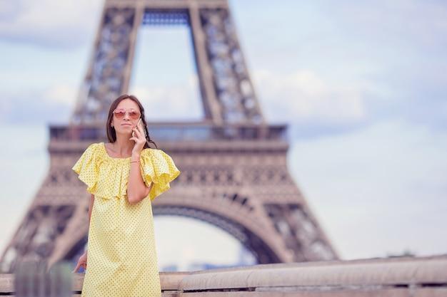 Jovem mulher falando por telefone na torre eiffel em paris Foto Premium