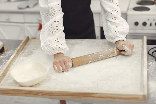 Jovem mulher fazendo biscoitos em forma de natal. sala de estar decorada com enfeites de natal ao fundo. mulher de avental. Foto gratuita