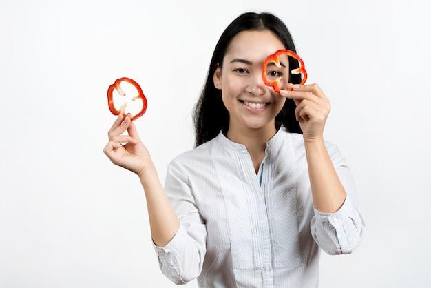 Jovem mulher fazendo cara engraçada com fatias de pimentão vermelho em fundo branco Foto gratuita