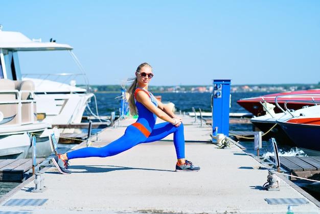 Jovem mulher fazendo esportes na doca Foto Premium