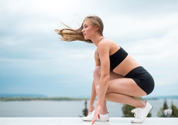 Jovem mulher fazendo exercícios de fitness tiro longo Foto gratuita