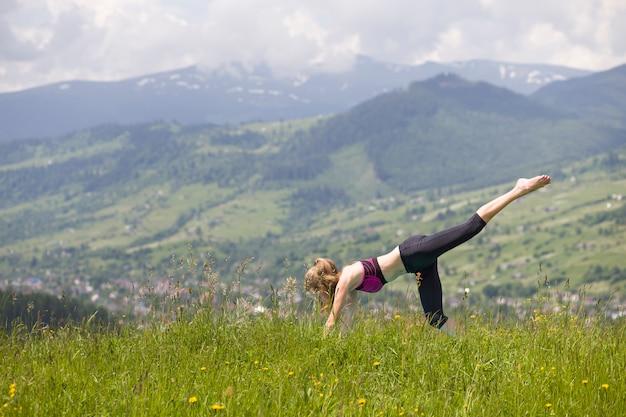 Jovem mulher fazendo exercícios de ioga ao ar livre. Foto Premium
