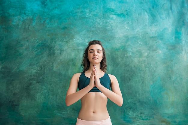 Jovem mulher fazendo exercícios de ioga na parede verde Foto gratuita