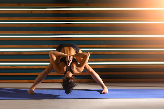 Jovem mulher fazendo exercícios de ioga no estúdio escuro. conceito de estilo de vida de saúde. Foto Premium