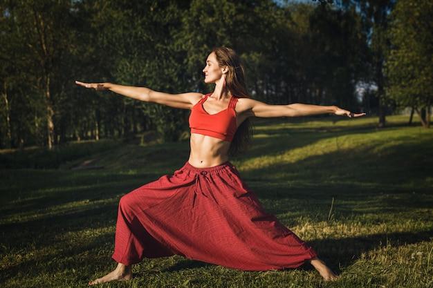 Jovem mulher fazendo exercícios de ioga no parque da cidade de verão Foto Premium
