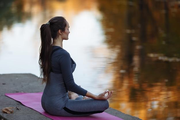 Jovem mulher fazendo exercícios de ioga no parque da cidade outono. conceito de estilo de vida de saúde. Foto Premium