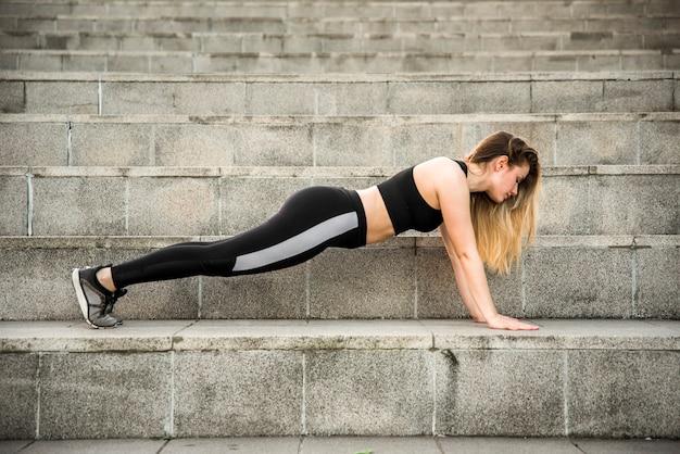 Jovem mulher fazendo exercícios na rua Foto gratuita