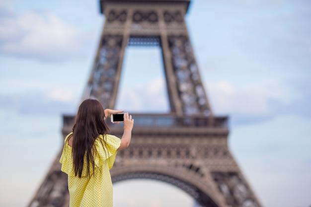 Jovem mulher fazendo foto por telefone na torre eiffel em paris Foto Premium