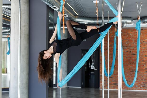 Jovem mulher fazendo ioga aérea na rede de suspensão azul no ginásio Foto gratuita