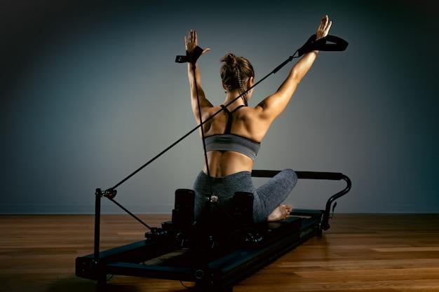 Jovem mulher fazendo pilates exercícios com uma cama de reformador. instrutor de fitness magro bonito. conceito de fitness Foto Premium