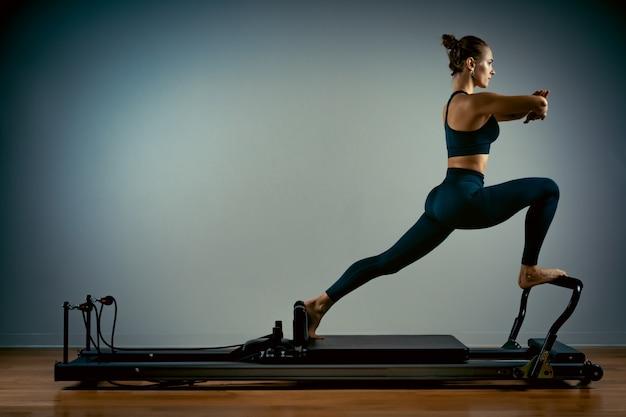 Jovem mulher fazendo pilates exercícios com uma cama de reformador. instrutor magro bonito da aptidão Foto Premium