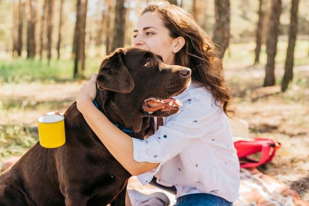 Jovem mulher fazendo um piquenique com seu cachorro Foto gratuita