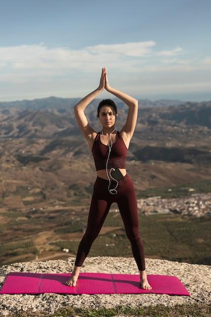 Jovem mulher fazendo yoga ao ar livre Foto gratuita