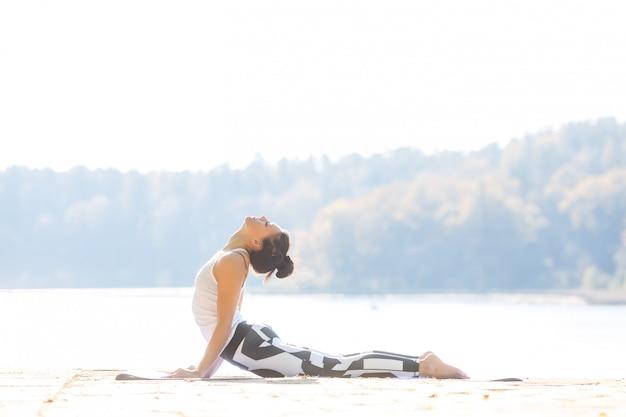 Jovem mulher fazendo yoga perto do lago ao ar livre, meditação. esporte fitness e exercício na natureza. pôr do sol de outono. Foto Premium