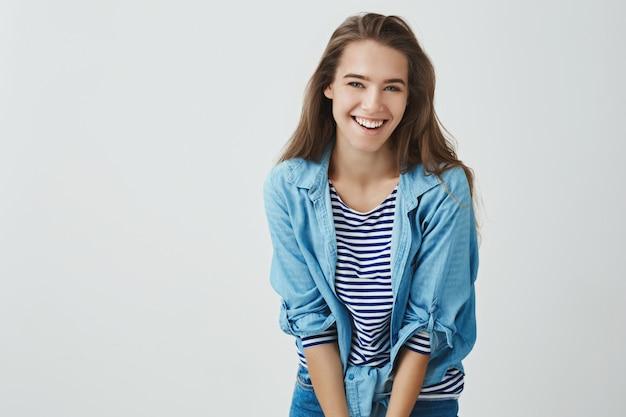 Jovem mulher feliz atrativa de sorriso que ri despreocupada se divertindo sorrindo alegremente dobra para a frente bobo bonito, levantando bobo. concurso europeu mulher rindo glamour olhando, em pé Foto gratuita