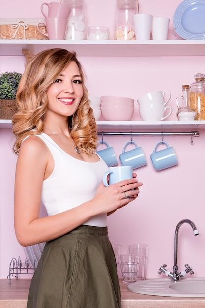 Jovem mulher feliz bebendo café ou chá em casa na cozinha. Foto Premium