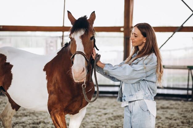 Jovem mulher feliz com cavalo no rancho Foto gratuita