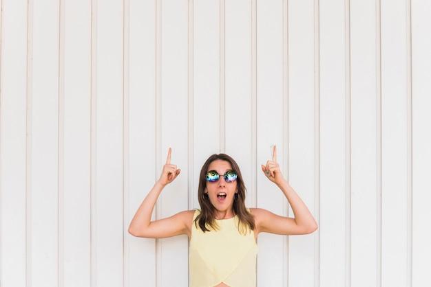 Jovem mulher feliz com polegares para cima posando em fundo branco Foto gratuita