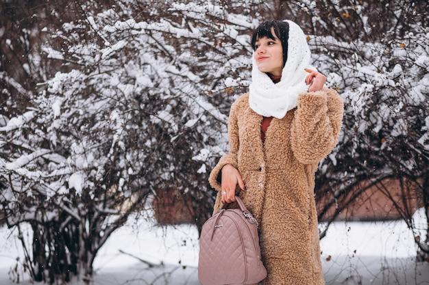Jovem mulher feliz em panos quentes em um parque de inverno Foto gratuita