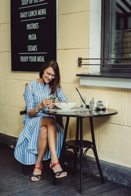 Jovem mulher feliz em um café de rua sorrindo risos bebendo café em um terraço Foto gratuita