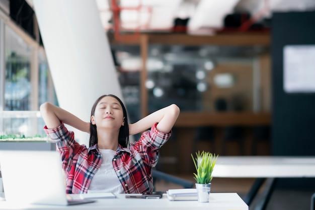 Jovem mulher feliz que descansa no escritório após o trabalho feito. Foto Premium