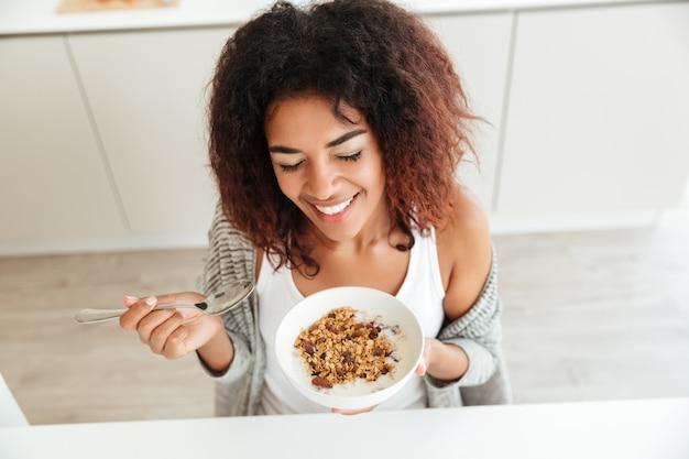 Jovem mulher feliz tomando café na cozinha Foto gratuita