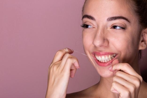 Jovem mulher fio dental dentes Foto gratuita