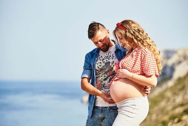Jovem mulher grávida andando com o marido contra vista para o mar Foto Premium