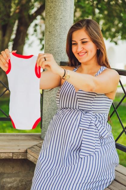 Jovem mulher grávida atraente. mulher grávida segurando um corpo de bebê. conceito de estilo de vida da cidade. Foto Premium