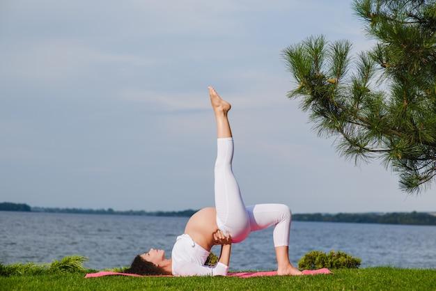 Jovem mulher grávida fazendo yoga ao ar livre Foto Premium