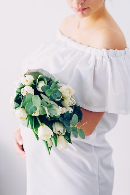 Jovem mulher grávida linda em um vestido branco com um buquê de tulipas brancas Foto Premium