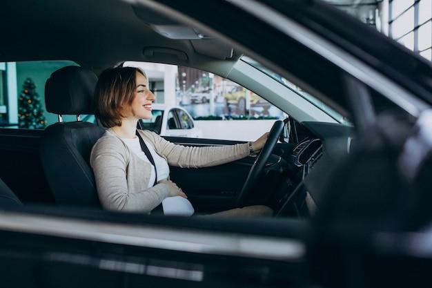 Jovem mulher grávida, testando um carro no carro showroom Foto gratuita