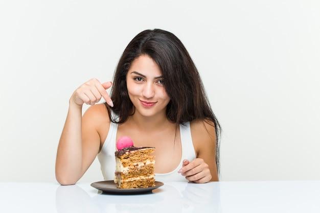 Jovem mulher hispânica, comendo um bolo de cenoura Foto Premium