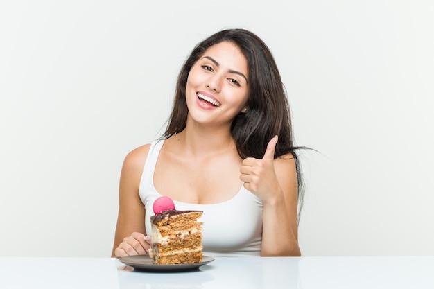 Jovem mulher hispânica, comendo um bolo, sorrindo e levantando o polegar Foto Premium
