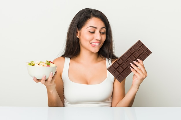 Jovem mulher hispânica, escolhendo entre tablete de maçã ou chocolate Foto Premium
