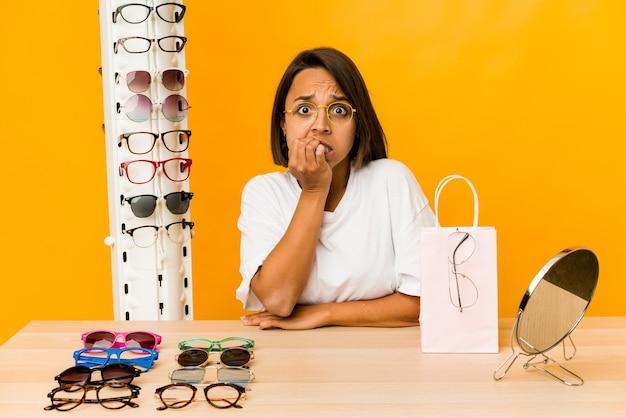 Jovem mulher hispânica experimentando óculos isolado roer as unhas, nervosa e muito ansiosa. Foto Premium