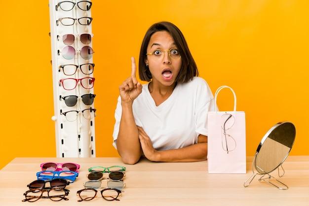 Jovem mulher hispânica experimentando óculos isolados, tendo uma ideia, o conceito de inspiração. Foto Premium