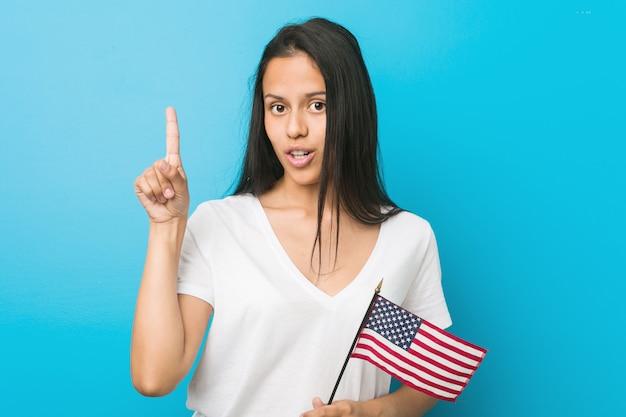 Jovem mulher hispânica, segurando uma bandeira dos estados unidos, tendo uma ótima idéia Foto Premium