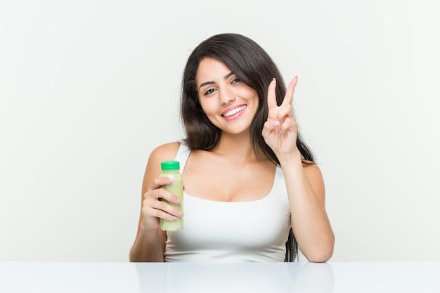 Jovem mulher hispânica, segurando uma bebida vegetal, mostrando o número dois com os dedos Foto Premium
