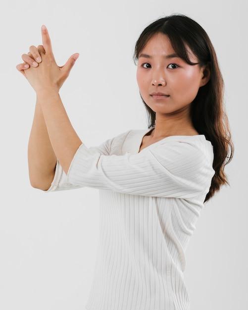 Jovem mulher imitando uma arma e olhando para a câmera Foto gratuita